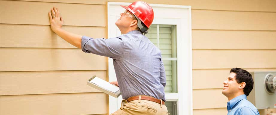 Home inspectors looking at the siding of a house