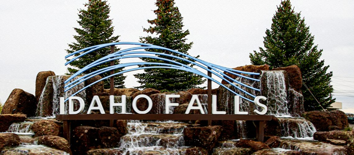 Idaho Falls sign with small waterfalls and three pine trees in the background.